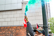 London, United Kingdom, May 22, 2021: A man holds a flare as other hold placards and banners outside Israeli Embassy in London on Saturday, May 22, 2021, as they take part in a rally supporting Palestinians. Egyptian mediators held talks Saturday to firm up an Israel-Hamas cease-fire as Palestinians in the Hamas-ruled Gaza Strip began to assess the damage from 11 days of intense Israeli bombardment. Among the groups in attendance were branches of the National Education Union, the Palestine Solidarity Campaign, Palestine Action and Stop The War Coalition. (Photo by Vudi Xhymshiti/VXP)