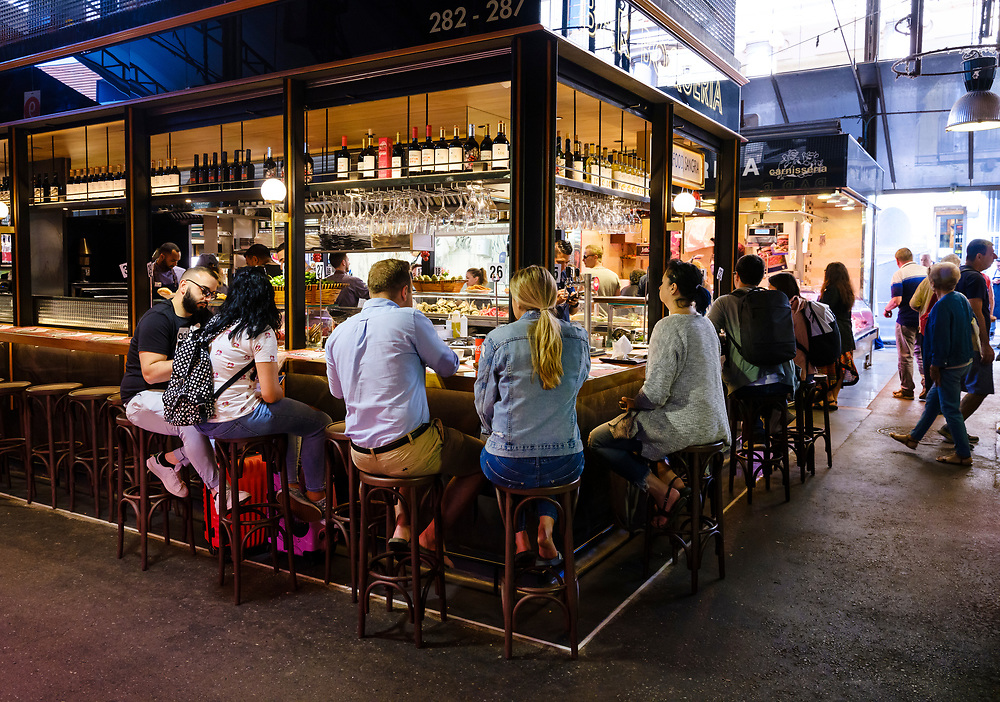 BARCELONA, SPAIN - CIRCA MAY 2018: People in La Boqueria enjoying Spanish Tapas. This is a large public market in the Ciudad Vieja district of Barcelona, Catalonia, Spain, and one of the city's foremost tourist landmarks.