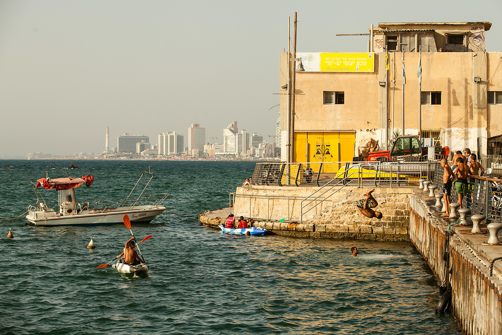 An Arab Israeli youth jumps to sea to enjoy the cool water on a hot summer day at Jaffa Port.
