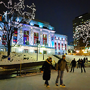 Ice skating rink in front of the Palais Montcalm in Quebec City's Old Town at night in winter.