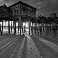B&W New England photography of a sunrise at Old Orchard Beach and its historic pier near Portland Maine. The sun was just crossed the horizon and created a beautiful sun star and rays. The long shadows of the wood pilings provided great leading lines into the frame. <br />
