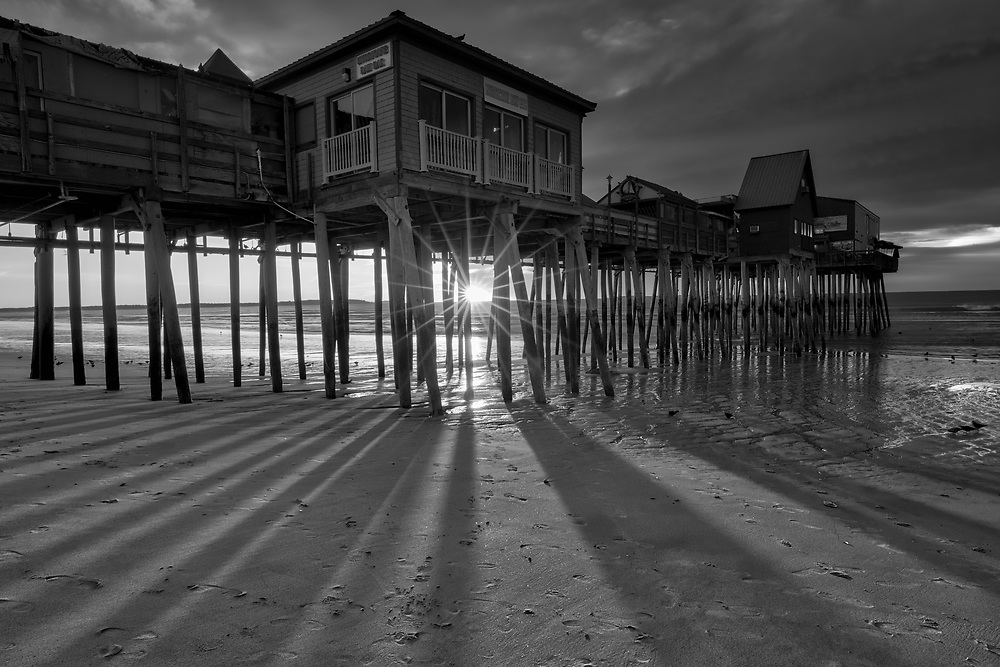 B&W New England photography of a sunrise at Old Orchard Beach and its historic pier near Portland Maine. The sun was just crossed the horizon and created a beautiful sun star and rays. The long shadows of the wood pilings provided great leading lines into the frame. <br /> <br /> New England black and white photos of Maine Old Orchard Beach Pier are available as museum quality photography prints, canvas prints, acrylic prints, wood prints or metal prints. Fine art prints may be framed and matted to the individual liking and decorating needs:<br /> <br /> https://juergen-roth.pixels.com/featured/historic-maine-old-orchard-beach-pier-juergen-roth.html<br /> <br /> Maine stock photography image licensing available at www.RothGalleries.com.<br /> <br /> Good light and happy photo making!<br /> <br /> My best,<br /> <br /> Juergen<br /> Photo Prints: http://www.rothgalleries.com<br /> Photo Blog: http://whereintheworldisjuergen.blogspot.com<br /> Instagram: https://www.instagram.com/rothgalleries<br /> Twitter: https://twitter.com/naturefineart<br /> Facebook: https://www.facebook.com/naturefineart