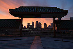 Former old Chinatown now east downtown rooftop view of the Houston, Texas skyline silhouette viewed through a pagoda with a colorful sunset.