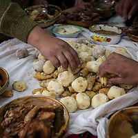 Hands reach for a shared Bolivian lunch including potatoes and oca tubers
