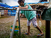 26 JANUARY 2018 - SANTO DOMINGO, ALBAY, PHILIPPINES: A woman water from a tank for evacuees from the Mayon Volcano living in tents at Barangay Lidong shelter. The shelter is in school and all of the classrooms are already being used to house evacuees. Recent arrivals are living in tents on the school grounds. The volcano was relatively quiet Friday, but the number of evacuees swelled to nearly 80,000 as people left the side of  the volcano in search of safety. There are nearly 12,000 evacuees in Santo Domingo, one of the communities most impacted by the volcano. The number of evacuees is impacting the availability of shelter space. Many people in Santo Domingo, on the north side of the volcano, are sleeping in huts made from bamboo and plastic sheeting. The Philippines is now preparing to house the volcano evacuees for up to three months.      PHOTO BY JACK KURTZ