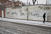 Dont worry be happy graffiti during freezing weather, dubbed The Beast from the East due to the sub zero cold temperature winds coming in from Siberia, descends on Kings Heath High Street on 1st March 2018 in Birmingham, United Kingdom.