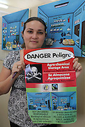 Olivia Avilez, Environmental Officer for the BSCFA, holds a poster issued to all sugar cane producers that illustrates the appropriate and inappropriate methods of arranging a storage room. Ms. Avilez is in charge of making sure Fairtrade standards are maintained by the associated sugar cane producers. Belize Sugar Cane Farmers Association (BSCFA), Orange Walk, Belize. January 21, 2013.