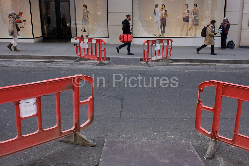 Four barriers positioned to help disabled public negotiate kerbs in Bond Street. Positioned strangely into the road, pedestrians walk by, one man in the centre carries as red bag, similar to the barriers. A Chanel shop can be seen in the background although the brand name is cropped out to make it more generic. Bond Street in central London is know for its jewellry and couture retailers and recent construction work has interrupted everyday life so ramps have been introduced to help wheelchair users.
