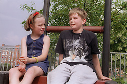 Young boy and girl sitting on play frame talking,