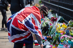 © Licensed to London News Pictures. 09/04/2021. LONDON, UK. A well wisher dressed in a Union flag lays flowers outside Buckingham Palace after the death of Prince Philip, aged 99, was announced.  Photo credit: Stephen Chung/LNP