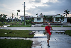 September 11, 2017 - Florida, U.S. - Local resident MARTIN PILOTE checks in with a friend on the phone in his driveway following Hurricane Irma at Marco Island. Pilote weathered the storm inside his home. (Credit Image: © Loren Elliott/Tampa Bay Times via ZUMA Wire)