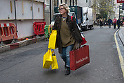 """Woman laden down with shopping bags on Bond Street, London, England, UK. Most exclusive shopping district in upmarket Mayfair. It has been a fashionable shopping street since the 18th century. Technically """"Bond Street"""" does not exist: The southern section is known as Old Bond Street, and the northern section, is known as New Bond Street. The rich and wealthy shop here mostly for high end fashion and jewellery."""
