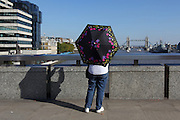 A tourist stops to take a photo of Tower Bridge from London Bridge, shading herself from the late September sun with an umbrella; people walking past stopped to see this strange sight.