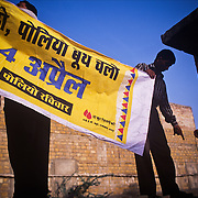 Day one of the April 2004 national campaign against polio: volunteers in Jaisalmer, western Rajasthan, are hanging posters of the campaign on the primary health center, PHC, from where the vaccine will be distributed to all the vaccinator teams.