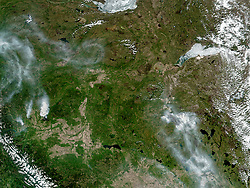 It has been more than two weeks since wildfires first broke out in Fort McMurray in the Canadian province of Alberta. The burned area continues to grow even larger, as fires are still spreading under warm, dry conditions.<br /> On May 15, 2016, the Visible Infrared Imaging Radiometer Suite (VIIRS) on the Suomi-NPP satellite captured a natural-color image (top) of active fires detected in Alberta and smoke that crossed into Saskatchewan. Red outlines indicate hot spots where VIIRS detected warm surface temperatures associated with fires.<br /> On the day this image was acquired, 15 wildfires burned around Fort McMurray. Nine of them were new fires, having ignited within the previous 24 hours. Two were burning out of control. The burned area's size - 2,510 square kilometers (970 square miles) - had grown somewhat, increasing by about four percent since a few days before, on May 12.<br /> The Operational Land Imager (OLI) on the Landsat 8 satellite acquired an higher resolution image (bottom) of the burn scar on May 12, when the burn area spanned about 2,410 square kilometers (930 square miles). The false-color image combines shortwave infrared, near infrared, and green light (OLI bands 7-5-3). With this combination, burned areas appear brown. Near- and short-wave infrared help penetrate clouds and smoke (white) to reveal the hot spots associated with active fires (red).<br /> The return of residents to Fort McMurray could be hampered by poor air quality, according to news reports. On May 16, the air quality index hit 38 on a scale that typically ranges from one to 10. A lower the number indicates a lower health risk.<br /> References<br /> Alberta Environment and Parks (2016, May 16) Air Quality Health Index. Accessed May 16, 2016.<br /> Alberta Government (2016, May 15) Update 15: Fort McMurray Wildfire (May 15 at 5:45 p.m.) Accessed May 16, 2016.<br /> Edmonton Journal (2016, May 16) Premier hints at delay in Fort McMurray re-entry because of extremely poor air quality. Accessed May 16, 2016.<br /> NASA image (top) by