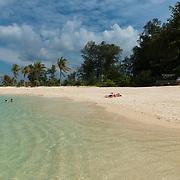 People sunbathing on Koh Lipe beautiful white sand beach, Thailand
