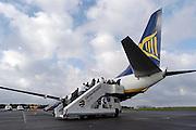 Duitsland, Laarbruch, 1-5-2003..Passagiers betreden een charter vliegtuig op de per 1-5-2003 in bedrijf gesteld airport Niederrhein. Vlak over de grens in Bergen N-Limburg vreest men voor geluidsoverlast. Drie keer per dag vliegt prijsbreker charter vliegmaatschappij Ryanair op Londen. Ook verwacht men veel lucht vrachtvervoer. Over twee maanden is de terminal klaar. Tot dan is aankomst en vertrek in de toekomstige hangar...Luchtvaart , economie, milieu, grensstreek, toerisme...Foto: Flip Franssen/Hollandse Hoogte