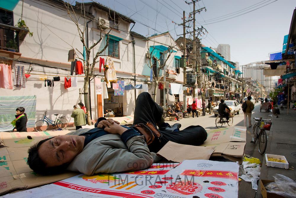 Man sleeps on cardboard in Zi Zhong Road, old Shanghai, China