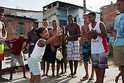 Young girl smiling and gesturing to a group of young men guys on a rooftop dancing passinho to funk Carioca, Baile funk, Vila Valquiere, West Zone Zona Oueste, Rio de Janeiro