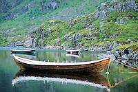 Reflection in water of small wooden row boat moored to shore of lake Ågvatnet (Aagvatnet) near the village of Å i Lofoten on the island of Moskenesøya, Lofoten islands, Norway