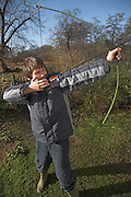 Model released picture of young boy holding a bow and firing an arrow, Suffolk, England, UK