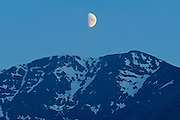 Half moon rising above mountain<br /> Stewart Cassiar Highway<br /> British Columbia<br /> Canada
