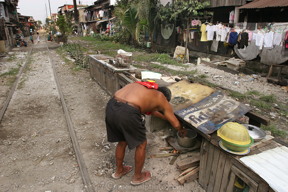 In Manila, any square foot of extra space finds a use for someone. Squatters even set up little kitchens on the median between train tracks and time their cooking to work around the train schedule. Manila, Philippines. (From a photographic gallery of kitchen images, in Hungry Planet: What the World Eats, p. 55)
