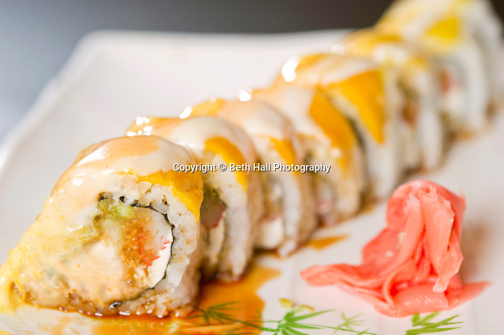 A roll topped with mango and sauce.