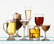 Various types of drinks on glass shelves against a white background