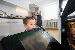 Father cooking food while hungry little boy is looking in oven