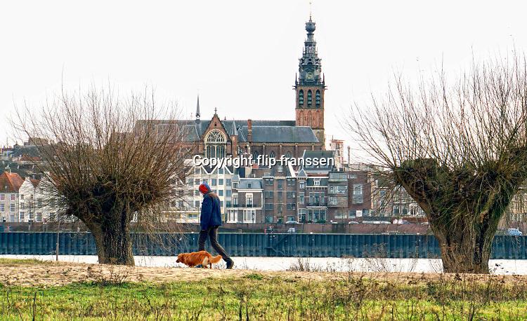 Nederland, Nijmegen, 4-3-2019 Een man loopt met zijn hond langs de oever van de Waal met op de achtergrond de waalkade en skyline van Nijmegen .Hij loopt op het lentereiland, eiland Lent, veurlent .Foto: Flip Franssen