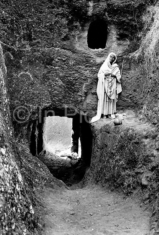 Ethiopian Orthodox pilgrims at Lalibela, Ethiopia. A Hermit  nun by the cave that is home, cut into the walls of the tunnels and passages that lead to Bet Giorgis, the most beautiful of the rock hewn churches. Lalibela in northern Ethiopia is famous for it's monolithic roack hewn churches and is one Ethiopia's holiest cities and a centre of pilgrimage for much of the country.