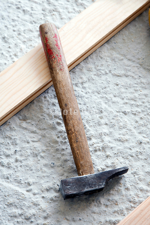 still life of a hammer on a cement floor with wood