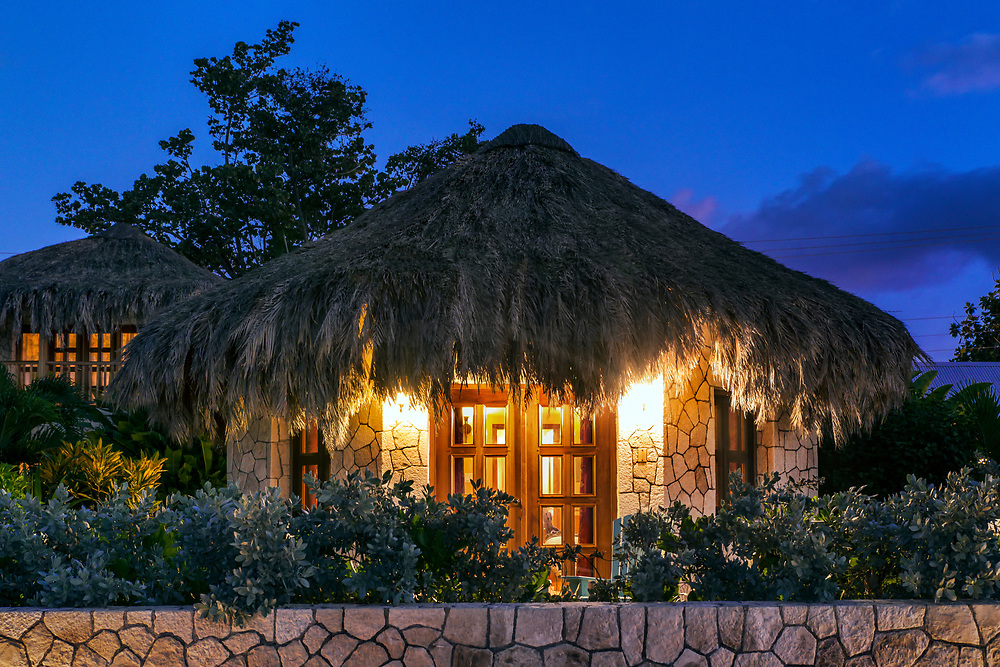 Boutique hotel cottages with thatched roof at night, Negril, Jamaica