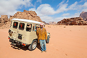 Sudanese Bedouin driver Ahmed poses proudly with his jeep in the desert in Wadi Rum, Jordan.