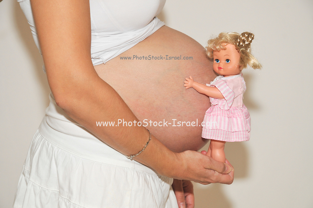 Woman, ninth month pregnancy with doll on belly Model Release Available