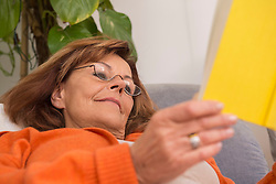 Senior woman reading a book while lying on sofa at home, Munich, Bavaria, Germany