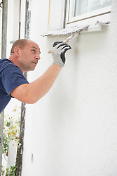Repairing painting wall man house outside
