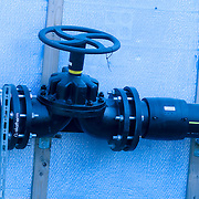 black pipe valve with blue tarp background