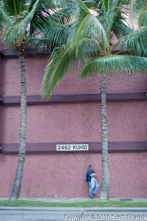 A man waiting along a wall in Waikiki.