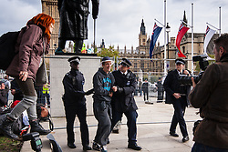 "Parliament Square, London, October 22nd 2014. Protesters from ""Occupy Democracy"" continue their demonstration against what they say is the hijacking of Britain's democracy by capitalism, where big business is allowed to trample people's rights. Having earlier been removed from Parliament square on grounds that they had damaged the threadbare lawn, they continue to demonstrate outside the closed off space. PICTURED: An occupy protester is led away by police who arrested him after he threw a bottle of water up to a protester ""besieged"" on the plinth of Churchill's statue."