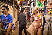 16 FEBRUARY 2013 - BANGKOK, THAILAND:    Men walk through Chatuchak Weekend Market in Bangkok. Chatuchak Weekend Market in Bangkok is reportedly the largest market in Thailand and the world's largest weekend market. Frequently called J.J., it covers more than 35 acres and contains upwards of 5,000 stalls.     PHOTO BY JACK KURTZ