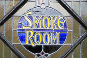 Close-up of stained glass window old vintage pub sign for Smoke Room, The Parrot public house, Aldringham, Suffolk, England, UK