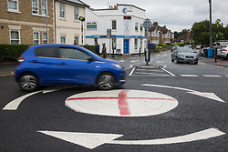 Windsor, UK. 10th July, 2021. A blue vehicle passes a mini-roundabout painted with the St George's flag. The Royal Borough of Windsor and Maidenhead repainted several roundabouts for safety reasons previously daubed with England flags before England's Euro 2020 quarter-final match against Ukraine but it appears that local residents have restored them in advance of the Euro 2020 final between England and Italy.