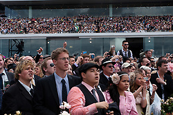 (c) under License to London News Pictures 02/11/2010. Young racegoers look on from the general public area as the runners in the 2010 Melbourne cup approach the finish line.