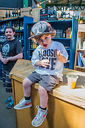 A young boy with a Choose Love t-shirt is taken on a tour by his father, buying juice, macaroons, beer and ice cream - The market reopening is signified by the ringing of the bell and is attended by Mayor Sadiq Khan. Tourists and locals soon flood back to bring the area back to life. London 14 Jun 2017