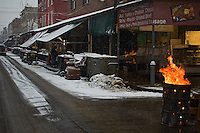 A portion of Philadelphia's Itallian Market on a snowy winter's morning as seen from the middle of 9th St. The fire in the 55 gallon drum serves to discard cardboard boxes, wood pallets and warm hands.