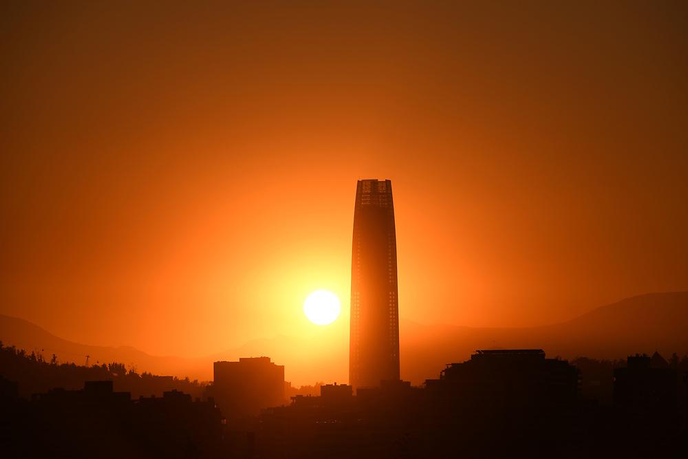 Sun setting behind a skyscraper in Santiago de Chile