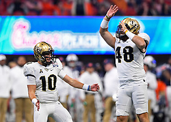 UCF Knights quarterback McKenzie Milton (10) celebrates his touchdown against Auburn University with teammate Mac Loudermilk (48) during the Chick-fil-A Peach Bowl NCAA college football game January 1, 2018, in Atlanta. (David Tulis via Abell Images for Chick-fil-A Peach Bowl)