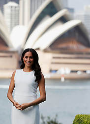 The Duchess of Sussex stands in the grounds of Admiralty House in Sydney, with a view of the Sydney Opera House, on the first day of the royal couple's visit to Australia.